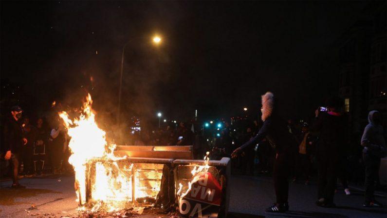 Manifestantes se paran cerca de una barricada en llamas en Filadelfia el 27 de octubre de 2020, durante una protesta. Cientos de personas se manifestaron en Filadelfia la noche del 27 de octubre, con saqueos y violencia. Los nuevos disturbios se produjeron un día después de la muerte de Walter Wallace, de 27 años, mientras portaba un cuchillo  (GABRIELLA AUDI/AFP vía Getty Images)