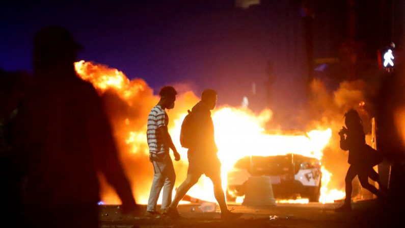 Los manifestantes caminan frente a un automóvil de la policía que se incendió durante una protesta en respuesta a la muerte de George Floyd, el 31 de mayo de 2020, en Boston, Massachusetts. (Maddie Meyer/Getty Images)