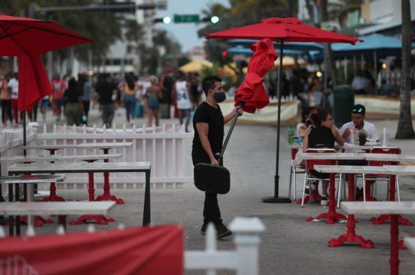 Un trabajador del restaurante del Boulevard Hotel quita un paraguas de la zona de asientos exteriores y se prepara para cerrar el restaurante por el día, ya que el 18 de julio de 2020 se establece un toque de queda de 8 p.m. a 6 a.m. en Miami Beach, Florida (EE.UU.). (Foto de Joe Raedle/Getty Images)