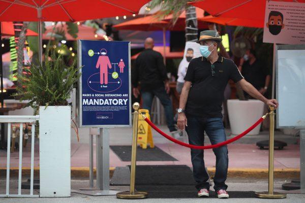 Juan Carlos, un anfitrión en el restaurante Ocean 10, se encuentra a la entrada del restaurante para rechazar a los clientes, ya que el 18 de julio de 2020 se establece un toque de queda de 8 p.m. a 6 a.m. en Miami Beach, Florida (EE.UU.). (Foto de Joe Raedle/Getty Images)