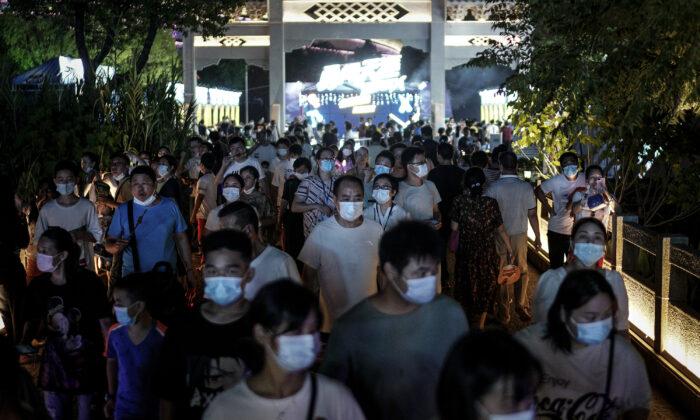 Los residentes usan máscaras mientras caminan por la entrada del Festival de la Cerveza de Wuhan, en la ciudad de Wuhan, provincia de Hubei, China, el 21 de agosto de 2020. (Getty Images)
