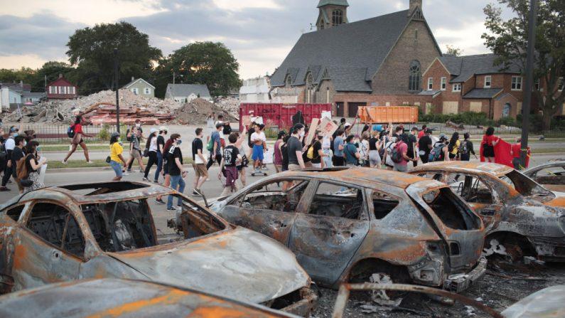 Un grupo de manifestantes protestaban frente a un lote de autos incendiados, el 28 de agosto de 2020, en Kenosha, Wisconsin. (Scott Olson/Getty Images)
