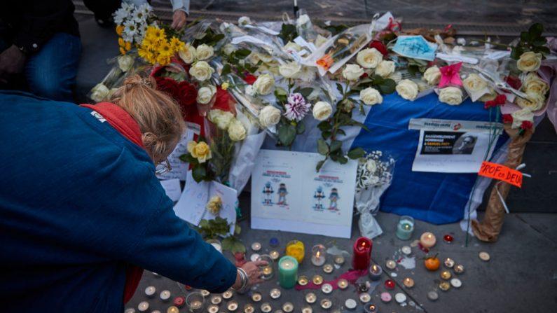 Una mujer enciende una vela por el maestro de escuela asesinado Samuel Paty durante una vigilia antiterrorista en la Place de La Republique el 18 de octubre de 2020 en París, Francia. (Foto de Kiran Ridley/Getty Images)