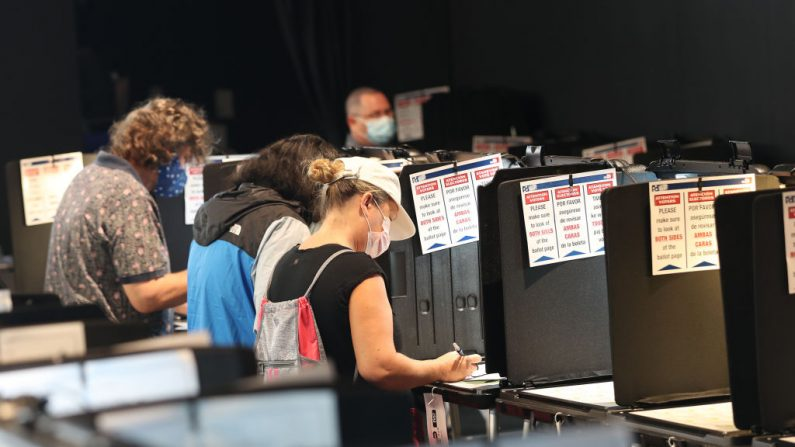 Los votantes llenan sus boletas mientras votan en el recinto del Museo de Ciencias Phillip y Patricia Frost el 19 de octubre de 2020 en Miami, Florida (EE.UU.). (Foto de Joe Raedle/Getty Images)