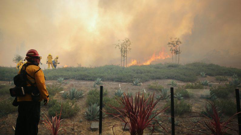 Un bombero trabaja mientras el incendio Silverado quema una casa en el condado de Orange el 26 de octubre de 2020 en Irvine, California. (Mario Tama/Getty Images)