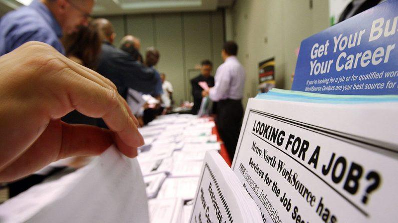Solicitantes de empleo miran folletos de ofertas de empleo en la exhibición WorkSource, el 14 de mayo de 2009 en Pasadena, California (EE.UU.). (David McNew/Getty Images)