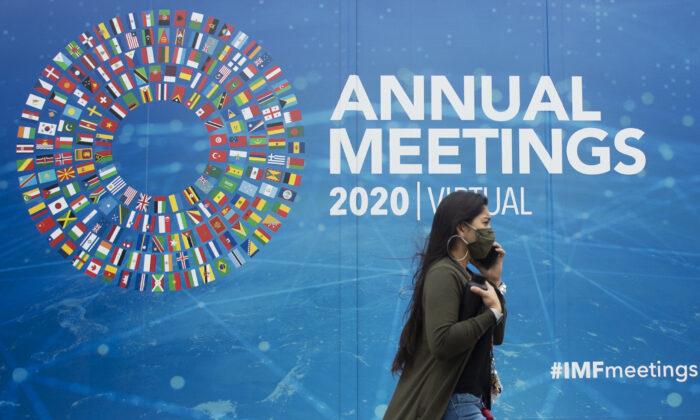 Una mujer pasa junto a un anuncio de las Reuniones Anuales virtuales 2020 afuera de la sede del Fondo Monetario Internacional en Washington, el 13 de octubre de 2020. (ANDREW CABALLERO-REYNOLDS/AFP a través de Getty Images)