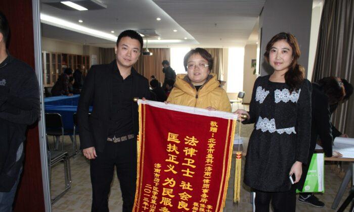 Los propietarios de inmuebles expresan su gratitud a Zhang Shichao (iz) por proteger sus derechos a través de medios legales, en Jinan, en noviembre de 2013. (Cortesía de Zhang Shichao)