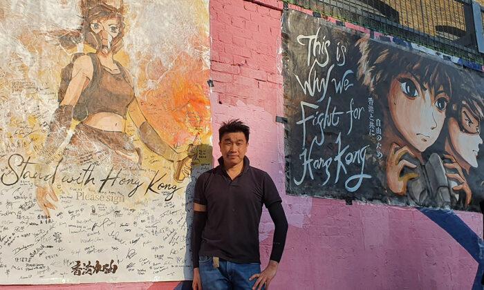 Otto Yuen, conocido en Hong Kong como el pintor de paredes de Lennon, posa con sus carteles pintados a mano en Londres, el 20 de septiembre de 2020. (Lily Zhou/The Epoch Times).