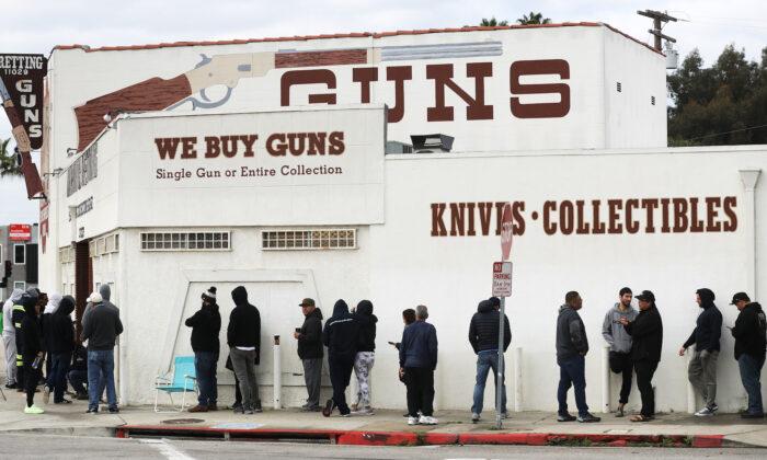 La gente hace cola frente a una tienda de armas en Culver City, California, el 15 de marzo de 2020. (Mario Tama/Getty Images)