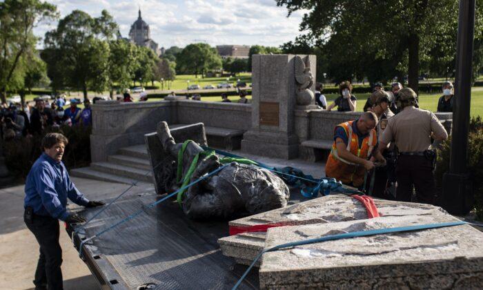 Una estatua de Cristóbal Colón, que fue arrojada al suelo por vándalos, es colocada en un camión en los terrenos del Capitolio del Estado en St. Paul, Minnesota, el 10 de junio de 2020. (Stephen Maturen/Getty Images)