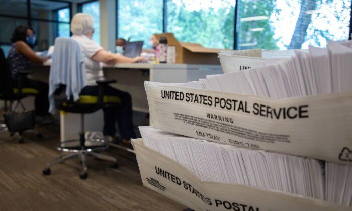 Grandes cajas de sobres se ven mientras los trabajadores electorales de votos en ausencia rellenan solicitudes de votos en la oficina de la Junta de Elecciones del Condado de Mecklenburg en Charlotte, Carolina del Norte, el 4 de septiembre de 2020. (Logan Cyrus/AFP vía Getty Images)