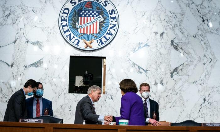 El presidente del Comité Judicial del Senado, Lindsey Graham (R-S.C.) y la miembro de rango del Comité Judicial del Senado, Dianne Feinstein (D-Ca.), se dan la mano luego del cuarto día del Comité Judicial del Senado en la audiencia de confirmación de la nominada a la Corte Suprema, Amy Coney Barrett, en el Capitolio de Washington el 15 de octubre de 2020. (Anna Moneymaker-Pool/Getty Images)