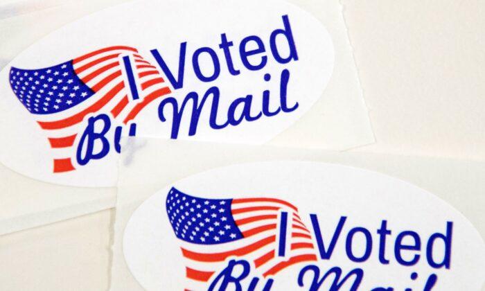"""Las calcomanías que dicen """"Yo voté por correo"""" se encuentran en una mesa esperando el 4 de septiembre de 2020 a que los trabajadores electorales de la Junta Electoral del Condado de Mecklenburg en Charlotte, Carolina del Norte, las peguen en los sobres. (Logan Cyrus/AFP vía Getty Images)"""