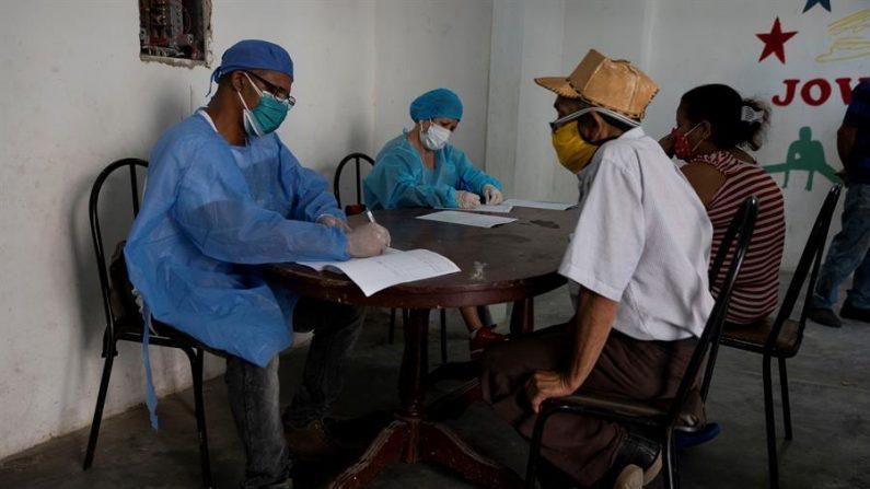 Dos médicos atienden a personas, el 25 de septiembre de 2020, durante una jornada de pruebas rápidas de covid-19, en Caracas (Venezuela). EFE/Rayner Peña R/Archivo