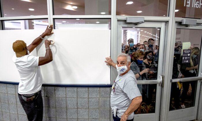 Trabajadores electorales tapan las ventanas del área de conteo de boletas del TCF Center en Detroit el 4 de noviembre de 2020. (Seth Herald/AFP vía Getty Images)