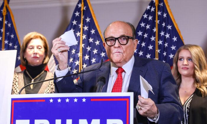 El abogado de Trump y exalcalde de la ciudad de Nueva York Rudy Giuliani habla con los medios mientras está flanqueado por la abogada de la campaña de Trump, Sidney Powell (izq.) y la asesora legal principal de la campaña de Trump, Jenna Ellis, en una conferencia de prensa en la sede del Comité Nacional Republicano, en Washington, el 19 de noviembre de 2020. (Charlotte Cuthbertson/The Epoch Times)