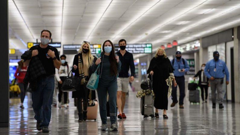 Unos viajeros caminan por el Aeropuerto Internacional Dulles de Washington en Dulles, Virginia, el 24 de noviembre de 2020. (Foto de NICHOLAS KAMM/AFP a través de Getty Images)