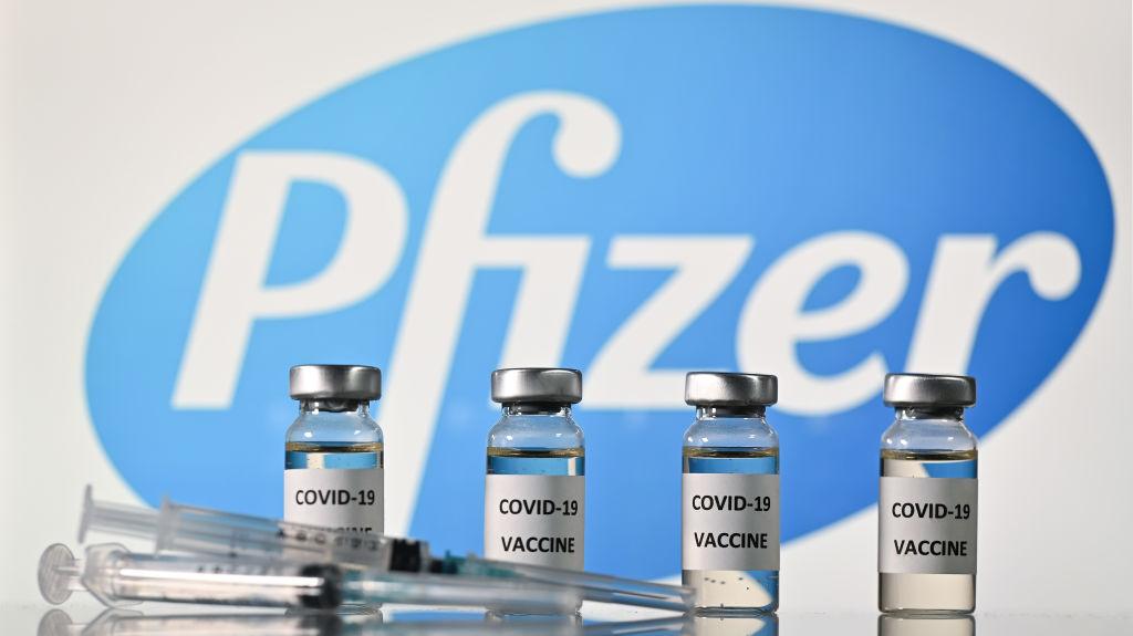 Una ilustración muestra frascos con adhesivos de vacuna contra la covid-19 adheridos y jeringas con el logotipo de la compañía farmacéutica estadounidense Pfizer, el 17 de noviembre de 2020. (Foto de JUSTIN TALLIS / AFP a través de Getty Images)