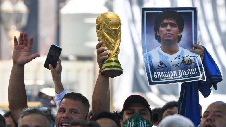 Un fan sostiene una fotografía de Diego Maradona y una réplica del trofeo de la copa del mundo mientras hace cola para para el velatorio en el palacio de Gobierno el 26 de noviembre de 2020 en Buenos Aires, Argentina. (Foto de Rodrigo Valle / Getty Images)