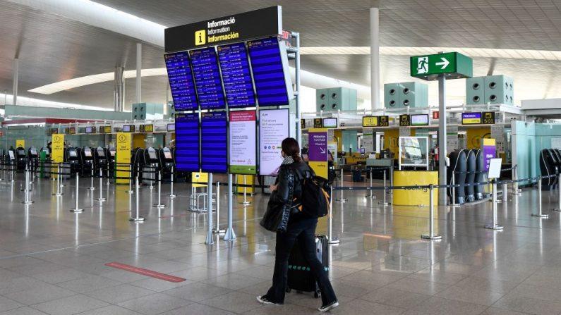 Una mujer mira paneles que muestran información de vuelo en la Terminal 1 del aeropuerto de El Prat en Barcelona (España) el 19 de noviembre de 2020. (Foto de PAU BARRENA / AFP a través de Getty Images)