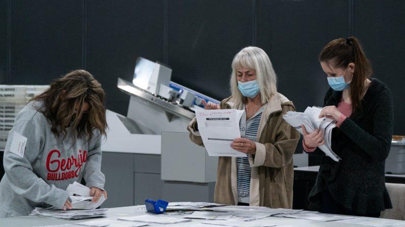El personal electoral en las oficinas de la Junta de Registro de Votantes y Elecciones del Condado de Gwinnett en Lawrenceville, Georgia, clasifica el 7 de noviembre de 2020 las solicitudes de boletas en ausencia para su almacenamiento. (Elijah Nouvelage/Getty Images)
