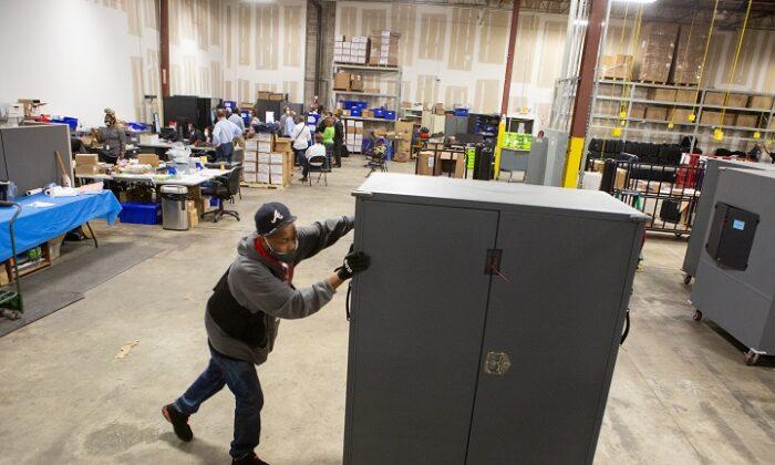 Un empleado del condado de Fulton mueve los transportadores de máquinas de votación para almacenarlos en el Centro de preparación para las elecciones del condado de Fulton, en Atlanta, Georgia, el 4 de noviembre de 2020. (Jessica McGowan/Getty Images)