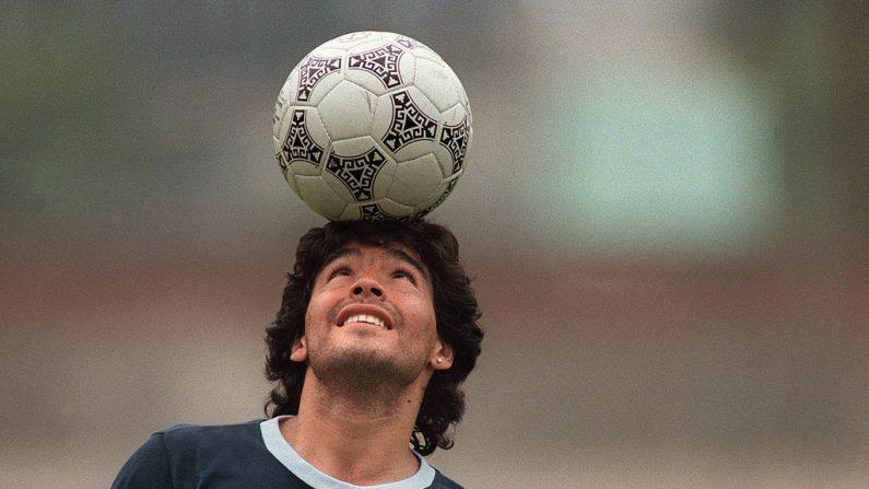 La estrella del fútbol argentino Diego Maradona, con un pendiente de diamantes, balancea una pelota de fútbol en su cabeza mientras camina fuera del campo de práctica después de la sesión de práctica de la selección nacional el 22 de mayo de 1986 en la Ciudad de México (México). (Foto de JORGE DURAN / AFP a través de Getty Images)