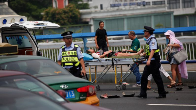 Esta foto tomada el 20 de agosto de 2018 muestra al personal médico que traslada a una mujer herida después de que un automóvil chocara contra motocicletas en Liuzhou, en la región sureña de Guangxi, en China. (Foto de archivo / AFP a través de Getty Images)