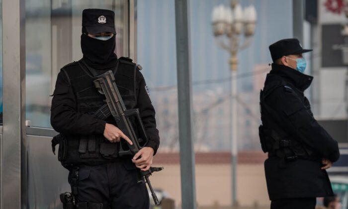 Oficiales de policía con el rostro cubierto aseguran un área en la estación de tren de Beijing el 27 de enero de 2020. (Nicolas Asfouri/AFP vía Getty Images)