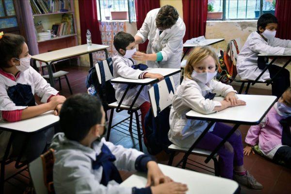 En esta imagen difundida por la agencia de noticias Adhoc, estudiantes de una escuela rural usan mascarillas en medio de la pandemia de covid-19 en Puntas de San Pedro, departamento de Colonia, Uruguay, el 22 de abril de 2020. (Foto de DANIEL RODRIGUEZ / adhoc / AFP a través de Getty Images)