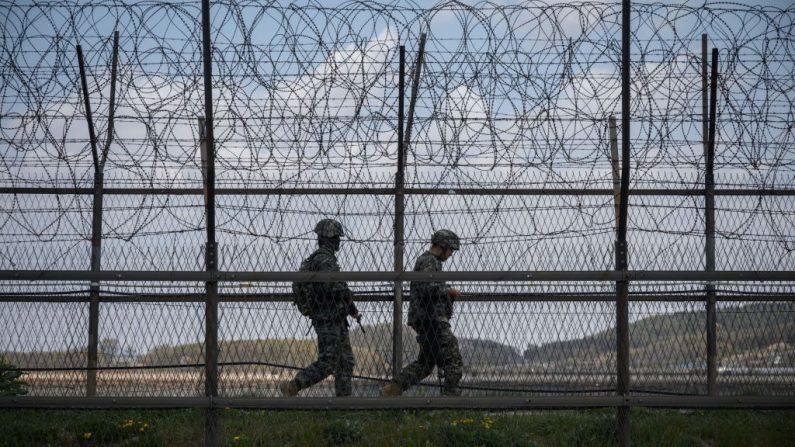 Soldados surcoreanos patrullan a lo largo de una cerca de alambre de púas Zona Desmilitarizada (DMZ) que separa Corea del Norte y Corea del Sur, en la isla surcoreana de Ganghwa el 23 de abril de 2020. (Foto de ED JONES / AFP a través de Getty Images)