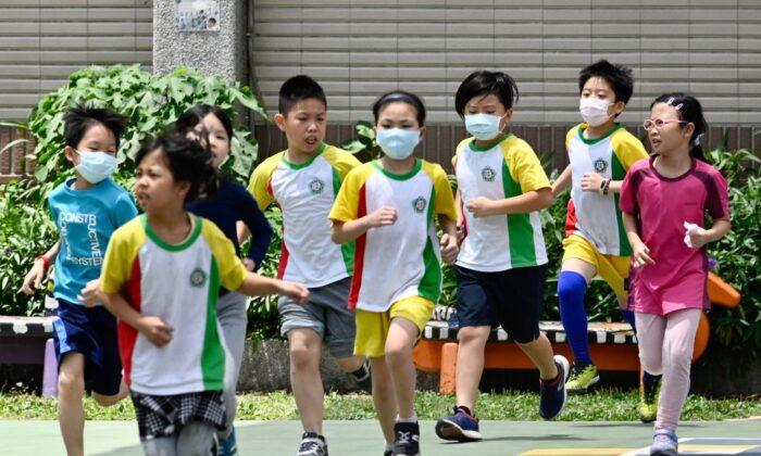 Estudiantes con máscaras corren durante una clase de deportes en la escuela primaria Dajia, en Taipei, el 29 de abril de 2020. (Sam Yeh/AFP a través de Getty Images)