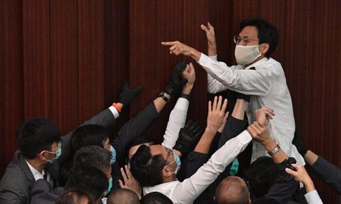 El legislador prodemocracia Eddie Chu Hoi-dick (arriba C) les grita a los de seguridad que intentan restringir en el Consejo Legislativo en Hong Kong el 8 de mayo de 2020. (Anthony Wallace/AFP a través de Getty Images)
