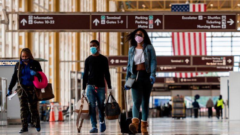 Los pasajeros caminan por un Aeropuerto Nacional Ronald Reagan Washington en Arlington, Virginia (EE.UU.), el 12 de mayo de 2020. (Foto de ANDREW CABALLERO-REYNOLDS / AFP a través de Getty Images)