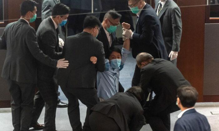 Guardias de seguridad expulsan del hemiciclo al legislador prodemocracia Ted Hui Chi-fung durante una refriega con los legisladores pro-Beijing en el Consejo Legislativo de Hong Kong el 22 de mayo de 2020. (Anthony Kwan/Getty Images)