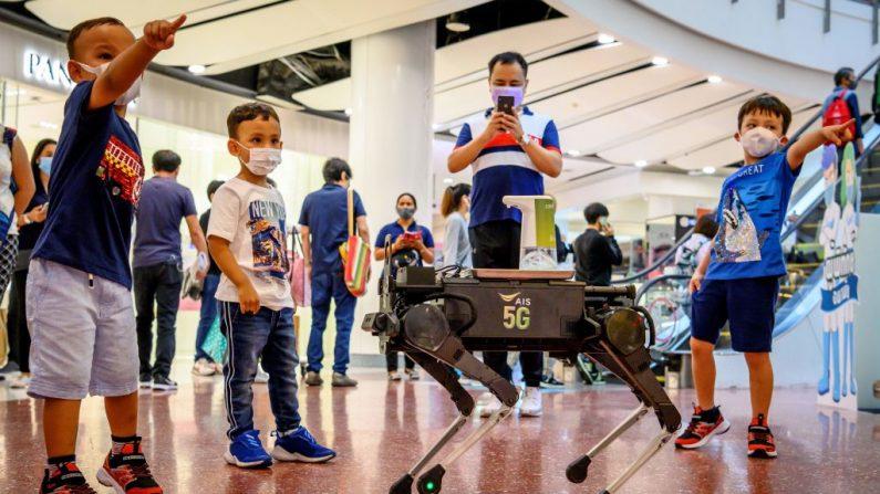 Niños juegan con un robot 5G K9 distribuyendo desinfectante de manos a los visitantes en un centro comercial de Bangkok, Tailandia el 4 de junio de 2020. (MLADEN ANTONOV/AFP vía Getty Images)