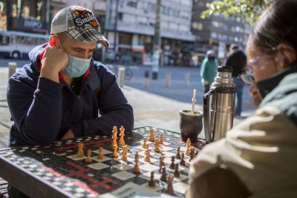 Dos hombres con mascarillas beben mate y juegan al ajedrez el 7 de mayo de 2020 en Montevideo, Uruguay. (Foto de Ernesto Ryan / Getty Images)