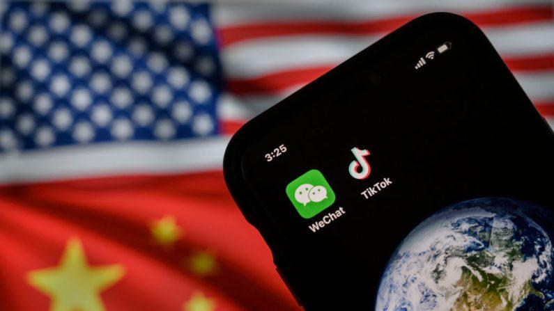 Un celular mostrando los logotipos de las apps chinas WeChat y TikTok frente a un monitor que muestra las banderas de Estados Unidos y China en una página de Internet, el 22 de septiembre de 2020 en Beijing, China. (Kevin Frayer/Getty Images)