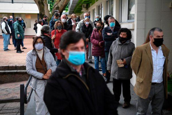 Personas hacen fila para emitir su voto en un colegio electoral en Montevideo el 27 de septiembre de 2020 durante las elecciones municipales y departamentales en medio de la pandemia del COVID-19. (Foto de EITAN ABRAMOVICH / AFP a través de Getty Images)