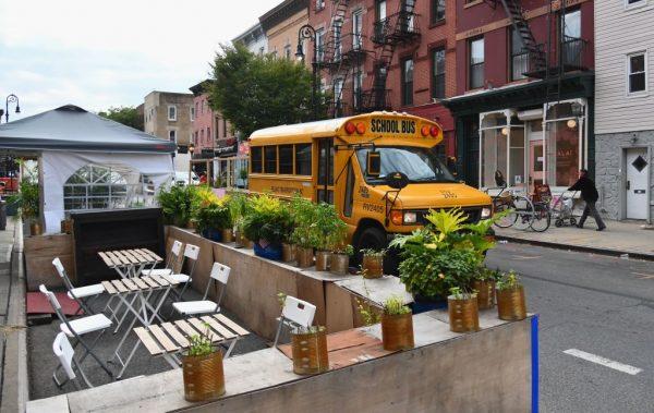Un autobús escolar pasa por las mesas vacías de un restaurante el 5 de octubre de 2020 en el distrito de Brooklyn de la ciudad de Nueva York (EE.UU.). (Foto de ANGELA WEISS / AFP a través de Getty Images)
