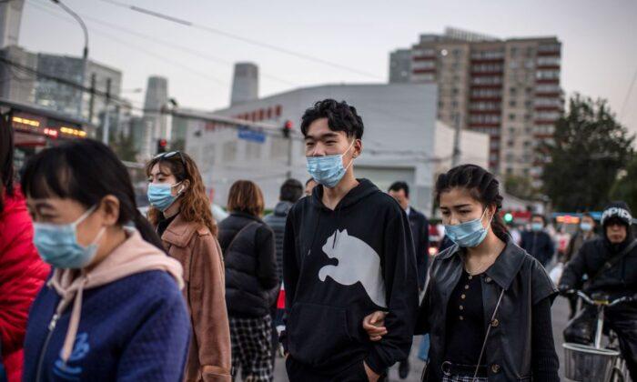 Personas con máscaras cruzan una calle durante la hora pico en Beijing, el 21 de octubre de 2020. (Nicolas Asfouri/AFP a través de Getty Images).