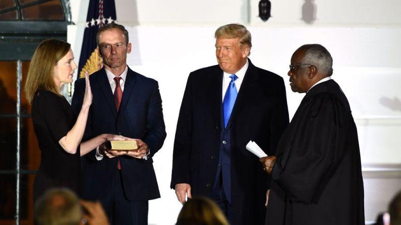 El presidente de EE. UU., Donald Trump, observa como el juez Asociado de la Corte Suprema, Clarence Thomas (der.), toma juramento a la jueza Amy Coney Barrett, como jueza Asociada de la Corte Suprema de EE. UU., acompañada por su esposo Jesse M. Barrett, durante una ceremonia en el Jardín Sur de la Casa Blanca el 26 de octubre de 2020, en Washington, DC.  (Foto de BRENDAN SMIALOWSKI/AFP a través de Getty Images)