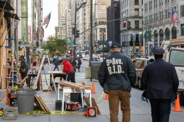 Empleado y guardia de seguridad pasan junto a un equipo de trabajadores que abordan una tienda en anticipación de los disturbios relacionados con las elecciones presidenciales, el 2 de noviembre de 2020 en la ciudad de Nueva York (EE.UU.). (Foto de David Dee Delgado / Getty Images)