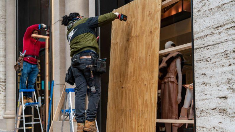 Los trabajadores abordan una tienda en previsión de los disturbios relacionados con las elecciones presidenciales, el 2 de noviembre de 2020 en la ciudad de Nueva York (EE.UU.). (Foto de David Dee Delgado / Getty Images)