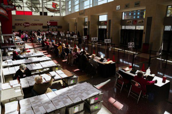 Los funcionarios electorales esperan a los votantes en el área de votación el 3 de noviembre de 2020 en Louisville, Kentucky (EE.UU.). (Foto de Jon Cherry / Getty Images)