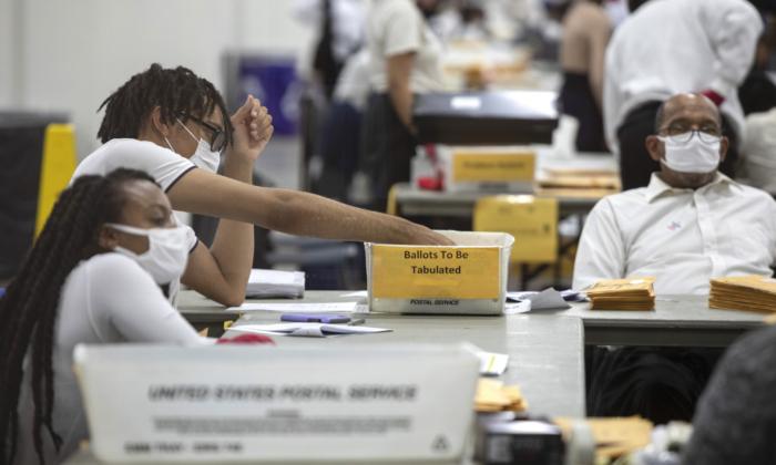 Un trabajador del Departamento de Elecciones de Detroit clasifica los votos ausentes en la Junta Central de Conteo en el TCF Center en Detroit, Michigan, el 4 de noviembre de 2020. (Elaine Cromie/Getty Images)