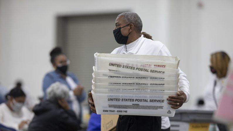 Un trabajador del Departamento de Elecciones de Detroit lleva cajas vacías que se utilizan para organizar las boletas de voto ausente después de acercarse al final del recuento de votos ausentes en la Junta Central de Conteo en el Centro TCF el 4 de noviembre de 2020 en Detroit, Michigan. (Elaine Cromie/Getty Images)