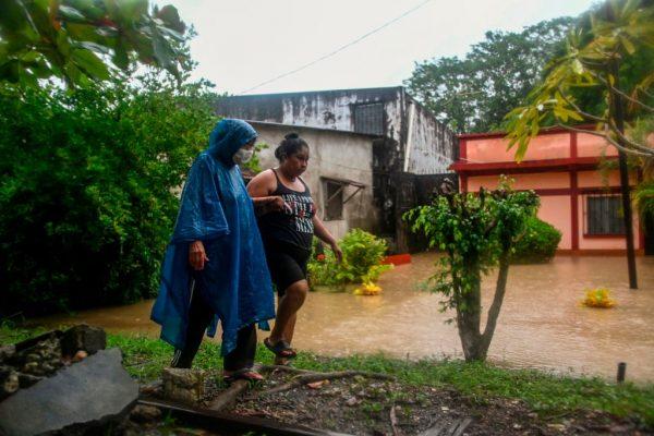 Mujeres caminan frente a una casa inundada debido a las fuertes lluvias causadas por el huracán Eta. (Foto de JOHAN ORDONEZ / AFP a través de Getty Images)
