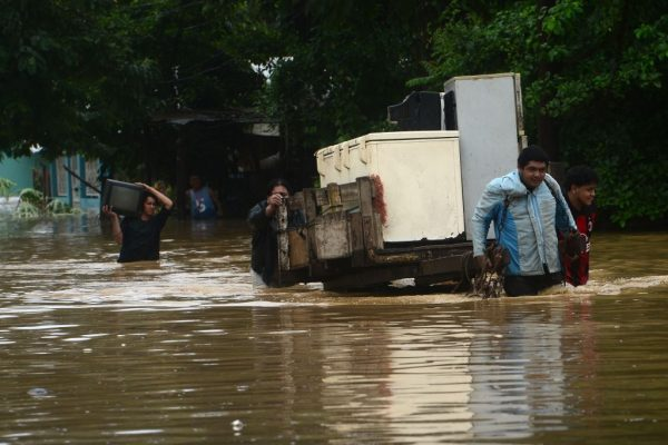 Residentes locales rescatan sus pertenencias luego del desborde del río Ulúa en el municipio de El Progreso, departamento de Yoro, Honduras el 5 de noviembre de 2020 debido a las fuertes lluvias provocadas por el huracán Eta. (Foto de ORLANDO SIERRA / AFP vía Getty Images)